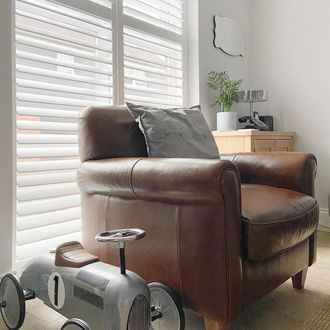 White shutters behind brown leather armchair with grey toy car