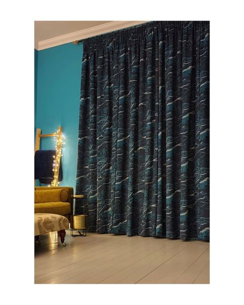 Light and dark blue print curtains hanging on windows of living room
