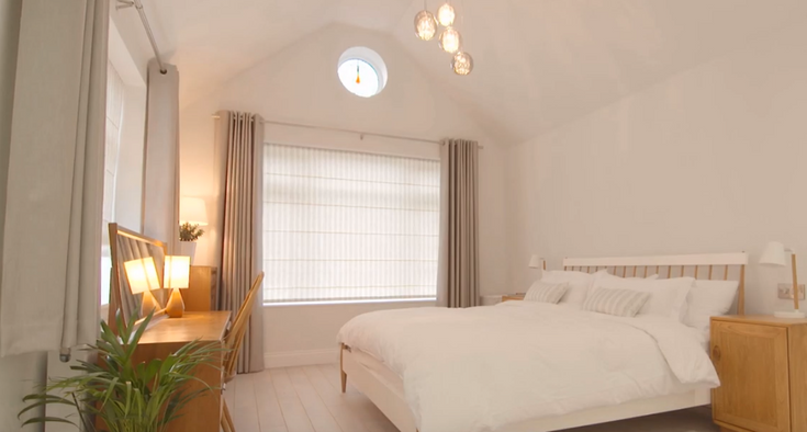 an image of white styled bedroom including a white blind that is fitted to a rectangular shaped window