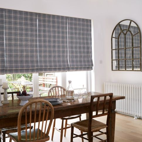 Check styled roller roman curtains fitted to a wide door window in a dining featuring a wood dining table and chairs