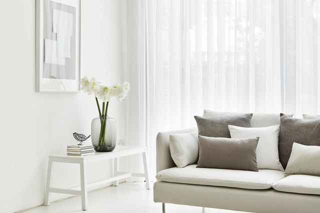 White curtains fitted to large windows in a living room decorated in white and features a sofa with grey and white cushions