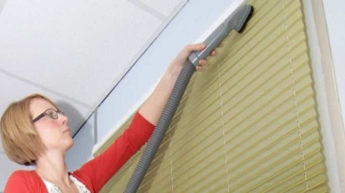 hoovering yellow venetian blinds