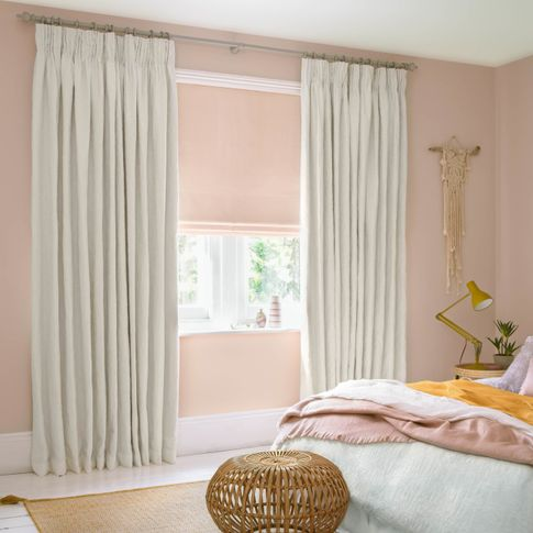 White curtains paired with blush roman blinds in a bedroom decorated in white and blush colours