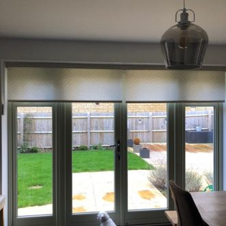 Zig zag pattern light blue motorised roller blinds installed on patio doors
