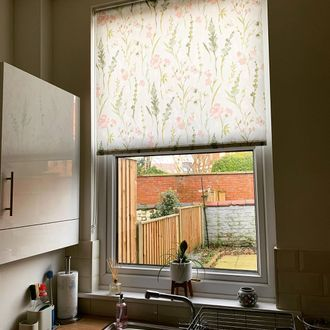 Roller blinds featuring penny rose print hanging on the kitchen window