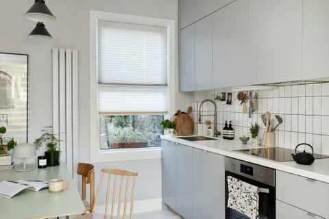 White pleated blinds paired with transitiom blinds on the same window in a kitchen decorated in white and grey colours