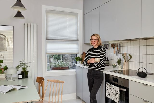 Someone standing in a white kitchen with white transition blinds fitted to rectangular window