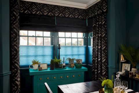Black roman blinds and teal pleatedblinds are fitted to the same rectangular windows along with gasoline decorated curtains in a dining team decorated with dark and blue colours
