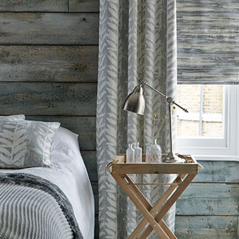 Grey Patterned Blackout Curtains in Isra Dove Fabric with a Grey Riviera Dusk Roman blind in the bedroom