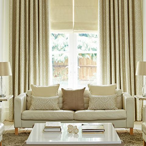 Living room with furniture, one large window and Kashmir Cream curtains combined with Tetbury Cream roman blinds