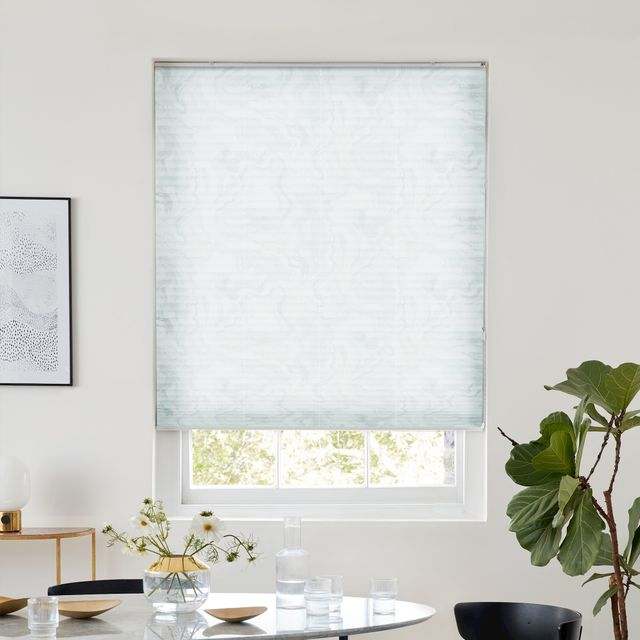 White pleated blind featuring very light ocean print dressed on window