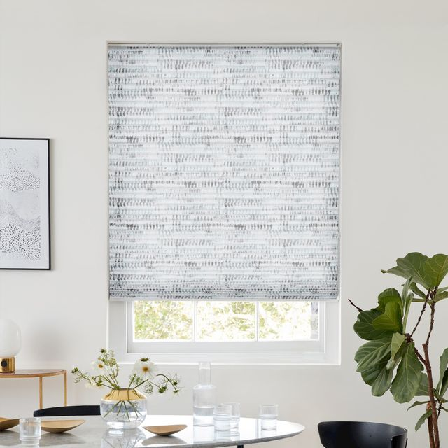 White pleated blind with grey natural print dressed on window