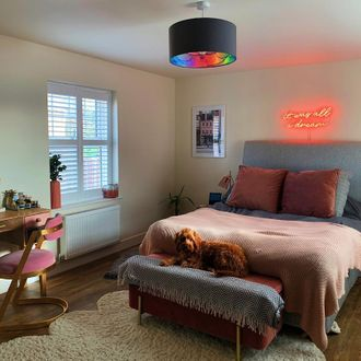 White shutters in modern bedroom with neon writing on wall and dog at the end of the bed