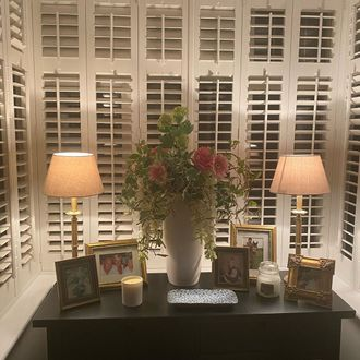Essential basswood/Windsor shutters in square bay window with two lamps and a vase of flowers