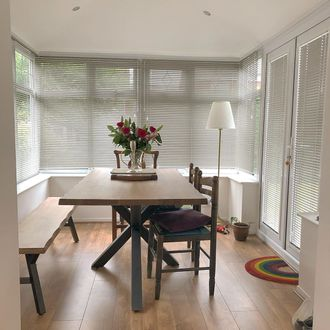 Grey perfect fit blinds with white lamp and large wooden table with bunch of flowers