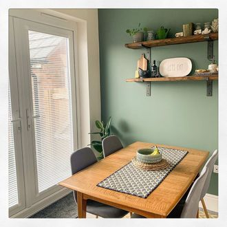 Snowflake perfect fit venetian on French doors with green wall and wooden table with fruit bowl