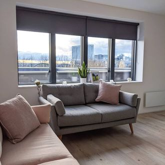 Acacia Gunmetal Roller blind on window with view of city behind grey sofa with pink cushion and pink sofa