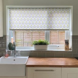 Petula Ochre Roller blind in kitchen behind wooden counter and white sink with green tiles and ceramic cacti