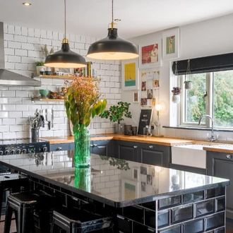Dark Grey roman blind in white and black tiled kitchen with grey cabinets