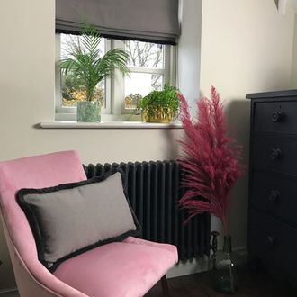 Garratt Peat Roman blind in modern dressing room with pink seat and black chest of drawers with a plant