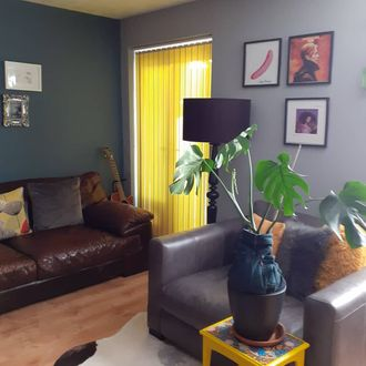 Yellow vertical blinds with guitar, brown leather sofa and black lamp