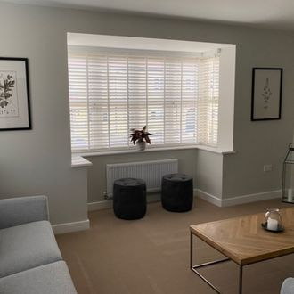 White shutters in a living room bay window with plant, two dark suede stools and a wooden coffee table