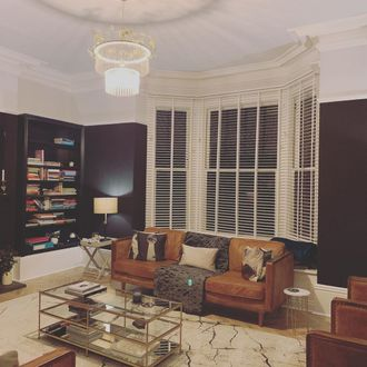 Wood white matte illusion blinds tall ceiling with navy walls, brown leather sofa and chandelier
