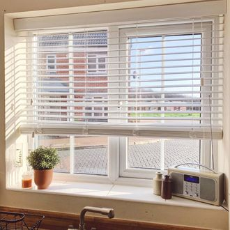 Illusion wood fine white blinds with plant pot and radio