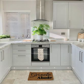 White wooden blinds in white kitchen with large plant and DIY doormat