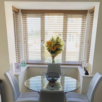 Wooden Venetian blinds in a square bay window with bouquet of flowers, 'new home' cards and glass dining table