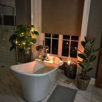 Beige roller blind in bathroom at night in front of shaped bath and plants, candles and prosecco glass