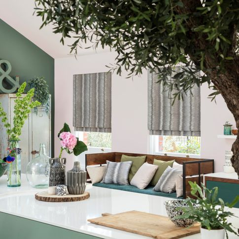 multicoloured striped roman blinds fitted to rectangular windows in a kitchen decorated in green and white