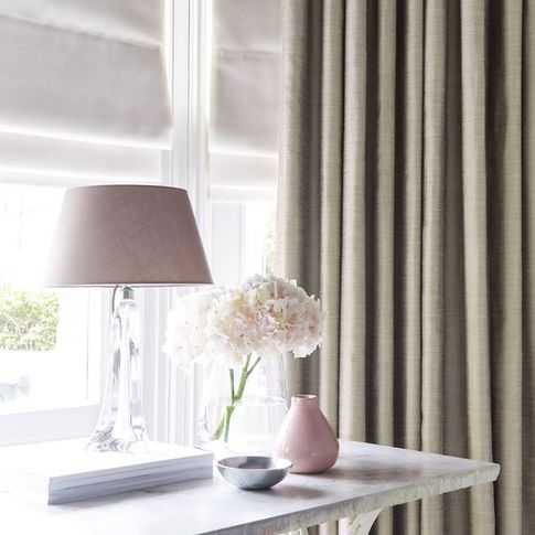 Off white coloured curtain matched with white roman blinds on a bay shaped window in a study with a lamp and flowers