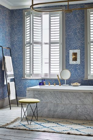 White tiered shutters in a blue and white patterned bathroom