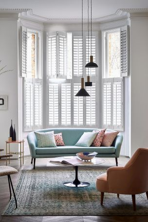 Tall tier-on-tier white Shutters sit behind a teal sofa in a spacious living room