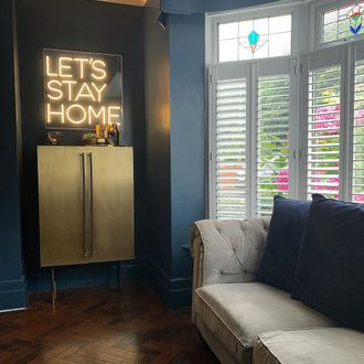 Pure White Shutters in living room with lets stay home sign