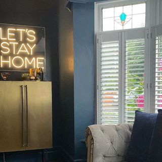 living room with dark blue walls and white shutters with a let's stay home neon sign