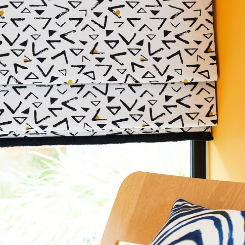 A close up image of the serraochre fringe noir nook roman blind fitted to a window in a room with yellow walls