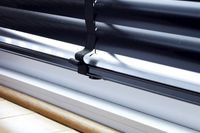 Black blind rail bar fitted to a window