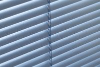 Blue coloured slats of a venetian blind