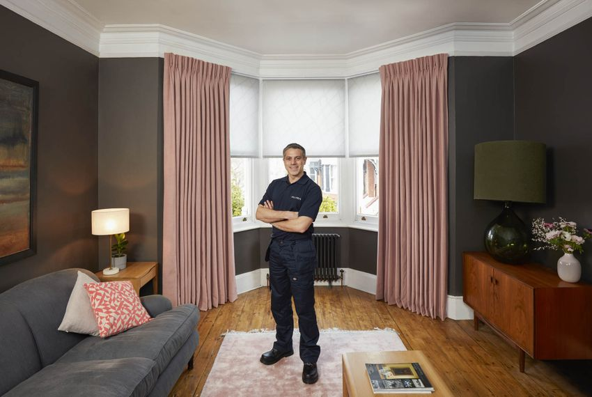 Advisor standing on pink rug infront of blush curtains over white roman blinds
