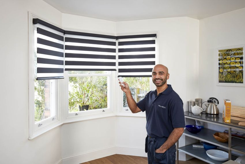 Advisor smiling with remote control in front of blue striped smart blinds