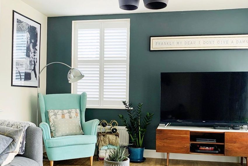 white shutters in living room with blue walls and small blue seat