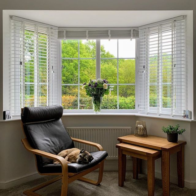 white Venetian blinds in bay window with leather arm chair with dog asleep on and vase of flowers in the windowsill.