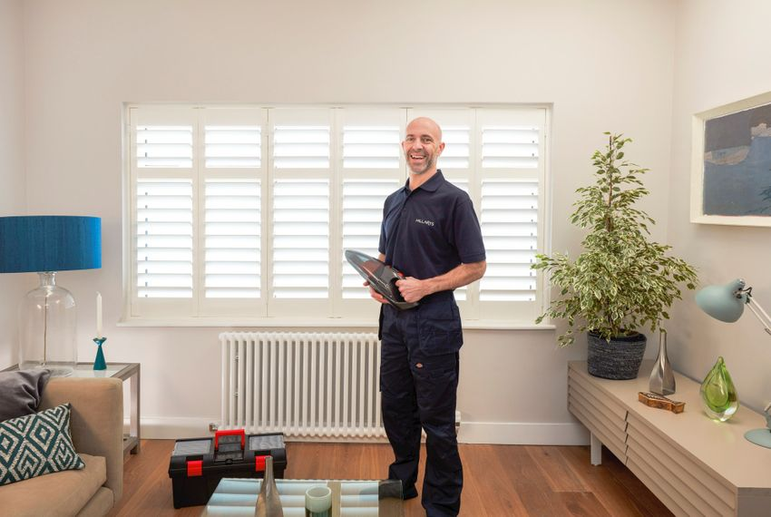 Advisor in front of white shutters and blue lamp