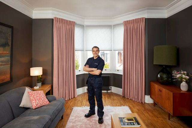 Advisor on pink rug in front of blush pink floor length curtains and white blinds