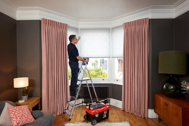 Advisor on ladder next to tool box installing white blinds behind pink curtains