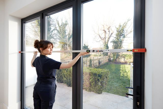 Female advisor measuring long glass windows out to garden