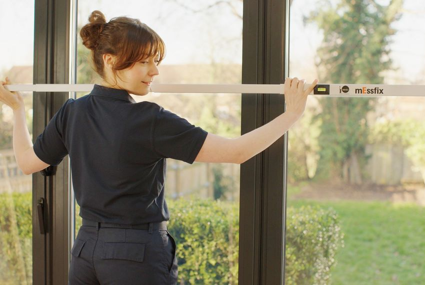 Female advisor looking over shoulder while measuring long glass windows