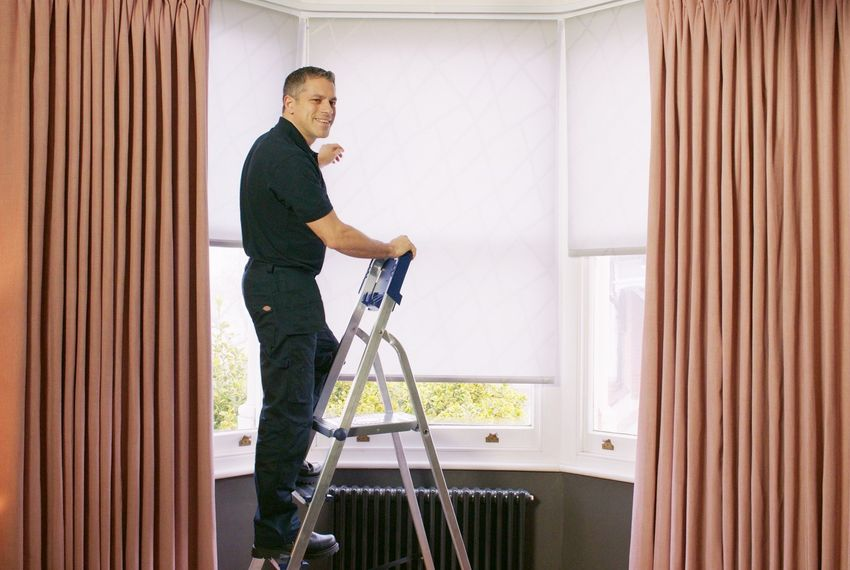 Advisor standing on ladder fitting white blinds behind blush pink floor length curtains